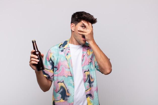 Młody mężczyzna z piwem wyglądający na zszokowanego, przestraszonego lub przerażonego, zakrywający twarz ręką i zerkający między palcami