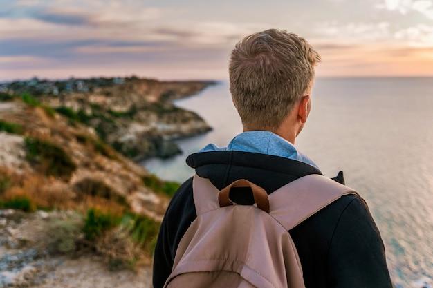 Młody mężczyzna z plecakiem podziwia zachód słońca na przylądku fiolent na krymie