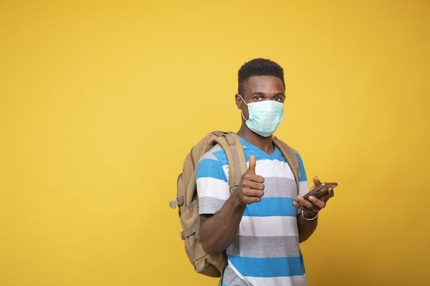 Młody mężczyzna z plecakiem w masce na twarzy i wykonujący gest kciuka w górę