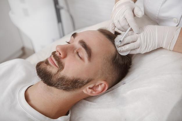 Młody mężczyzna z problemem wypadania włosów otrzymuje zastrzyki w skórę głowy przez lekarza trychologa