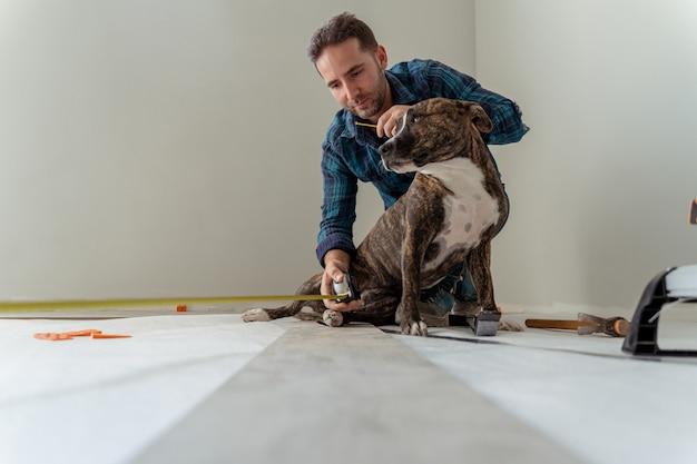 Młody mężczyzna z psem instaluje drewnianą podłogę w domu remont