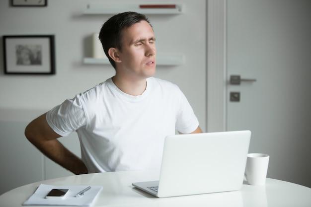 Młody mężczyzna z rękami na plecach, rozciągając po pracy na laptopie