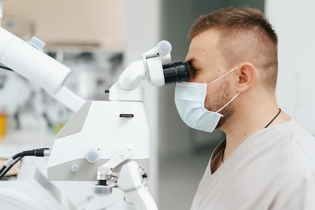 Młody mężczyzna z śliniakiem dla pacjenta na fotelu dentystycznym i dentystą, który siedzi obok niego. patrzy na zęby pod mikroskopem dentystycznym, trzyma wiertło dentystyczne i lusterko.