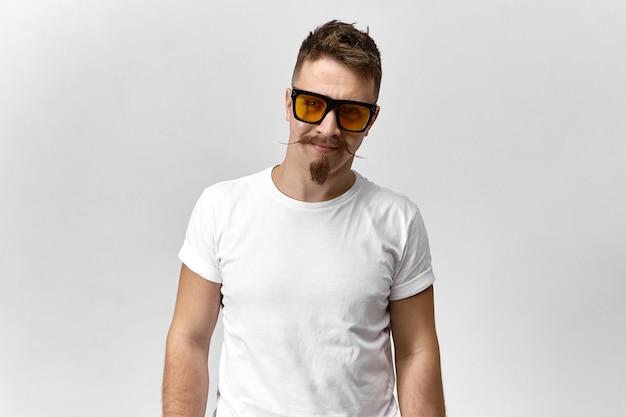 Młody mężczyzna z stylową brodą i wąsami, uśmiechając się na sobie żółte okulary