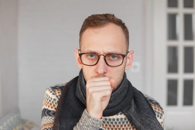 Młody mężczyzna z szalikiem na szyi kaszle z powodu zimna i bólu gardła