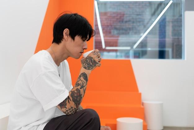 Młody mężczyzna z tatuażami przy filiżance kawy w kawiarni