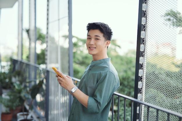Młody mężczyzna z telefonem komórkowym w domu na tarasie