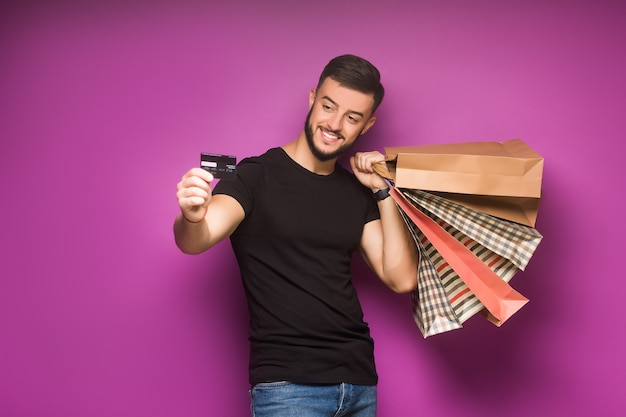 Młody mężczyzna z torbami na zakupy i kartą kredytową w rękach pozuje na fioletowym tle