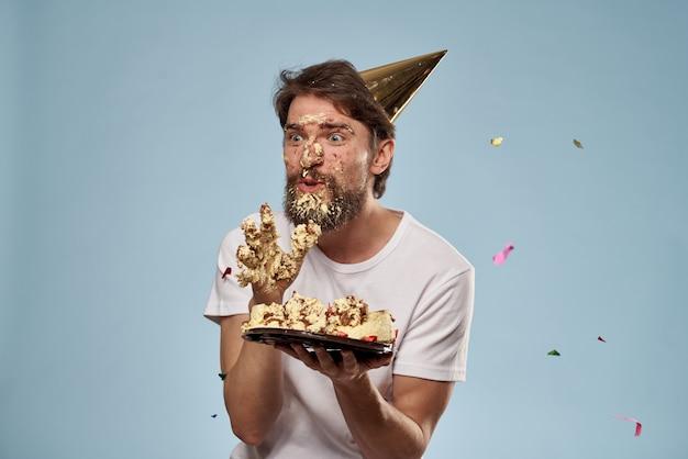 Młody mężczyzna z tortem urodzinowym spadł na twarz z ciastem, twarz w ciastku