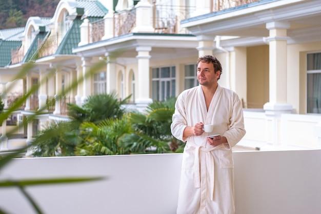 Młody mężczyzna z uśmiechem na twarzy w białym szlafroku stoi na otwartej werandzie hotelu w parku z filiżanką porannej herbaty lub kawy.