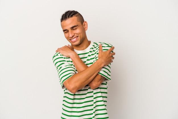 Młody mężczyzna z wenezueli na białym tle przytula się, uśmiechając się beztrosko i szczęśliwie.