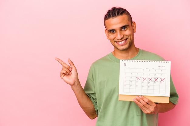 Młody mężczyzna z wenezueli trzyma kalendarz na białym tle na różowej ścianie, uśmiechając się i wskazując na bok, pokazując coś w pustej przestrzeni.