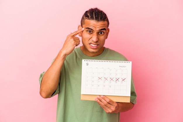 Młody mężczyzna z wenezueli trzymający kalendarz na białym tle na różowej ścianie pokazujący gest rozczarowania palcem wskazującym.
