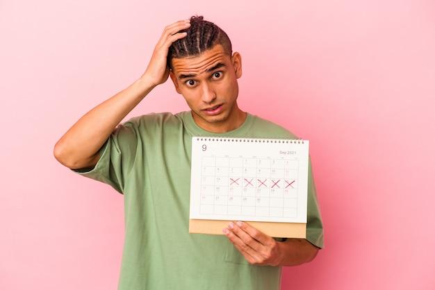 Młody mężczyzna z wenezueli trzymający kalendarz na białym tle na różowym tle będąc w szoku, przypomniała sobie ważne spotkanie.
