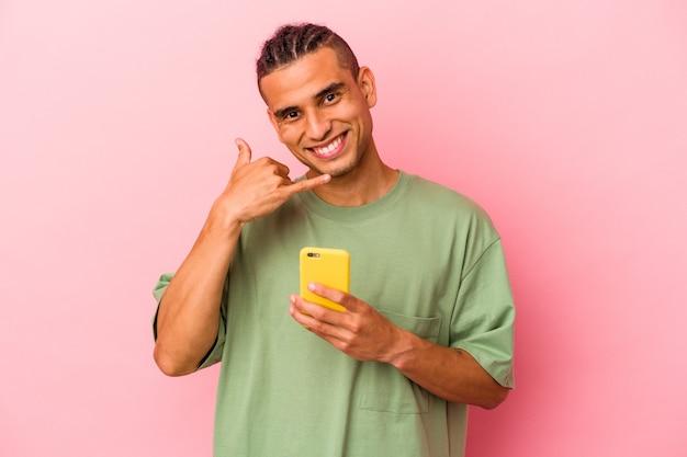 Młody mężczyzna z wenezueli trzymający telefon komórkowy na białym tle na różowym tle pokazujący gest połączenia z telefonem komórkowym palcami.