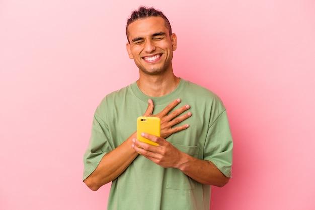 Młody mężczyzna z wenezueli trzymający telefon komórkowy na białym tle na różowym tle śmieje się głośno, trzymając rękę na klatce piersiowej.