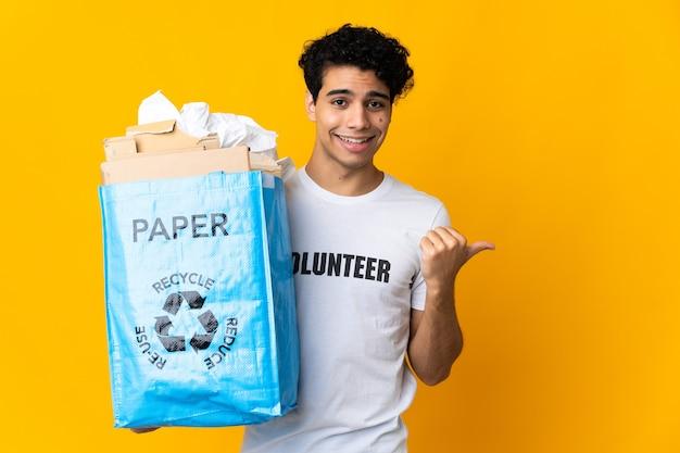 Młody mężczyzna z wenezueli trzymający worek recyklingu pełen papieru do recyklingu, wskazując na bok, aby przedstawić produkt