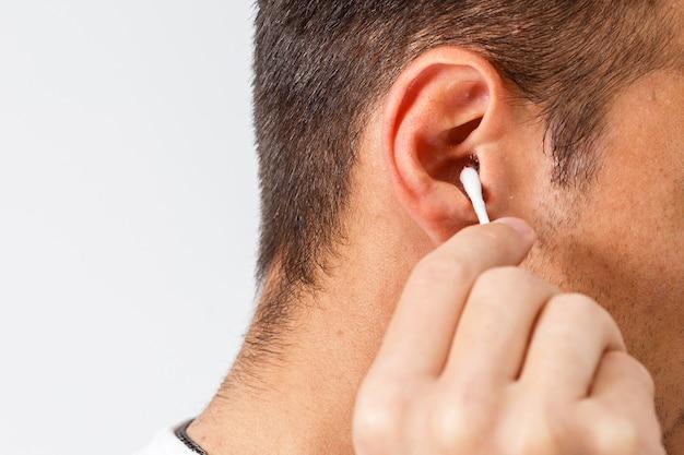 Młody mężczyzna z włosiem za pomocą izolowanych patyczków do uszu