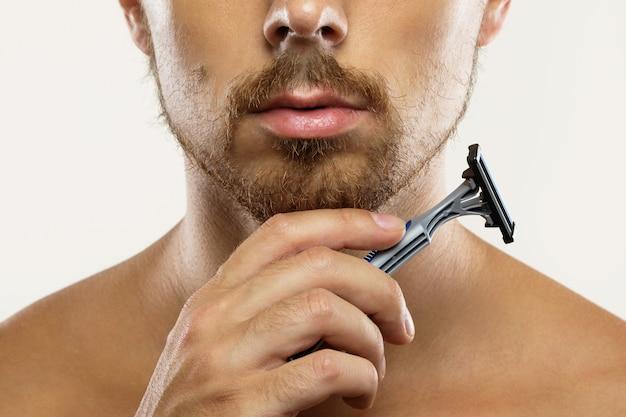Młody mężczyzna z zaniedbaną brodą przed rutynowym goleniem