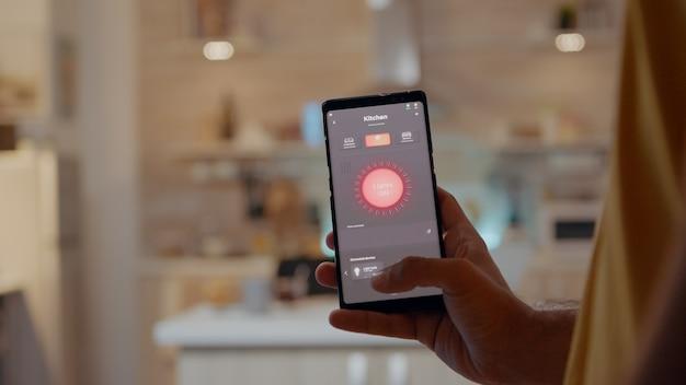 Młody mężczyzna za pomocą aplikacji inteligentnego domu dotyka ekranu, aby włączyć światło przez telefon komórkowy...