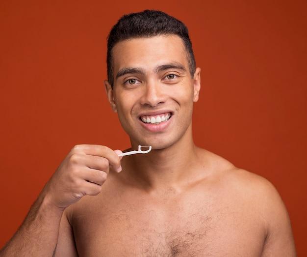 Młody mężczyzna za pomocą nici dentystycznej