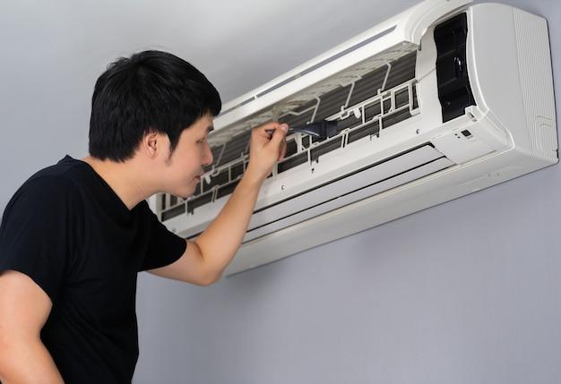 Młody mężczyzna za pomocą pędzla do czyszczenia klimatyzatora w pomieszczeniu na dopracowaniu