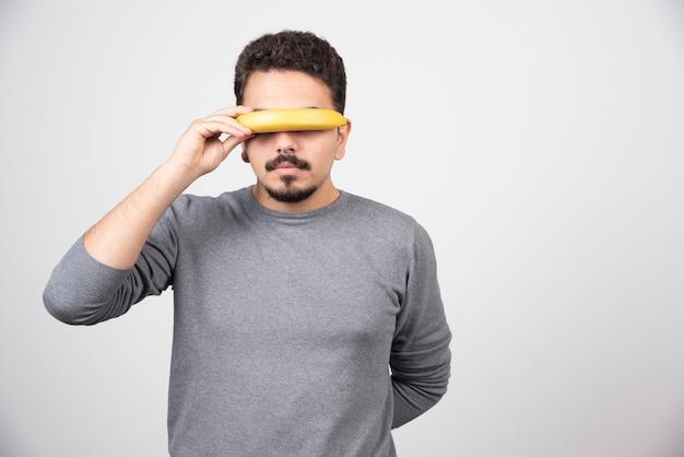 Młody mężczyzna zakrywający oczy bananem.