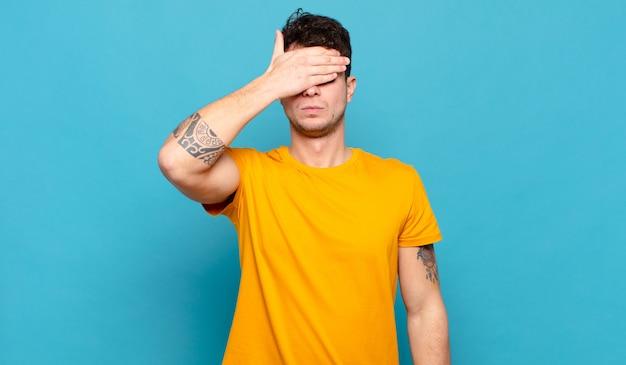Młody mężczyzna zakrywający oczy jedną ręką czujący się przestraszony lub niespokojny, zastanawiający się lub na ślepo czekający na niespodziankę