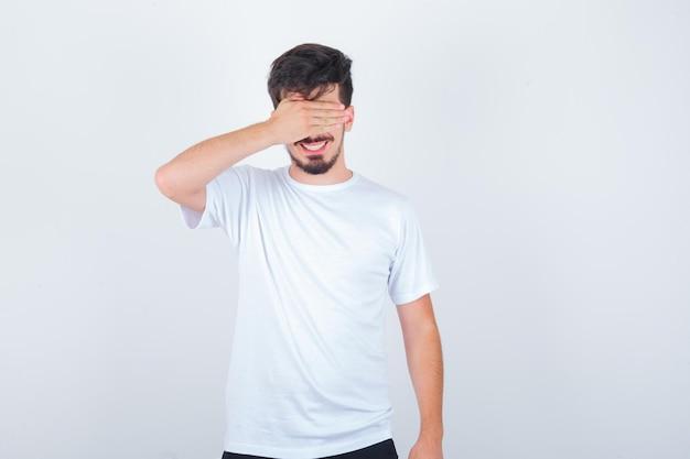 Młody mężczyzna zakrywający oczy ręką w koszulce i wyglądający uroczo