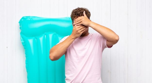 """Młody mężczyzna zakrywający twarz obiema rękami mówi """"nie""""! odmawianie zdjęć lub zakaz zdjęć. koncepcja wakacji"""