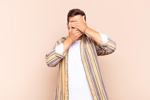 """Młody mężczyzna zakrywający twarz obiema rękami mówiąc """"nie"""" do aparatu! odmawianie zdjęć lub zakaz zdjęć"""