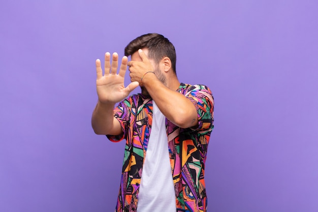 Młody mężczyzna zakrywający twarz ręką i wyciągający drugą rękę do góry, aby się zatrzymać, odmawiając zdjęć lub obrazków
