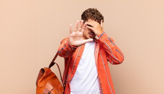 Młody mężczyzna zakrywający twarz ręką i wyciągający drugą rękę do przodu, aby zatrzymać aparat, odmawiając zdjęć lub zdjęć. koncepcja studenta