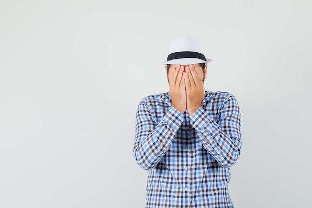 Młody mężczyzna zakrywający twarz rękami w kraciastej koszuli, kapeluszu i wyglądający na przestraszonego, widok z przodu.