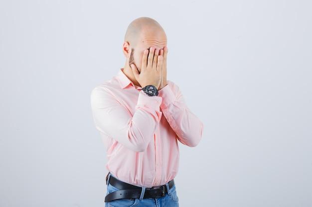 Młody mężczyzna zakrywający twarz rękami