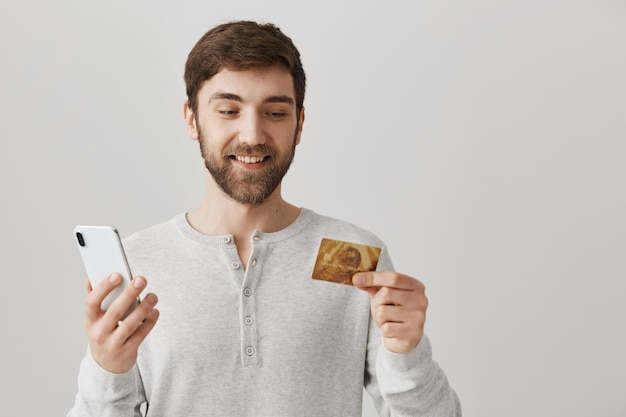 Młody mężczyzna zamawia online kartą kredytową, używając telefonu komórkowego