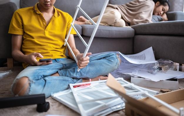 Młody mężczyzna zamierzający zamontować półkę w salonie w domu.