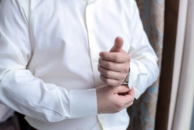 Młody mężczyzna zapina guziki na rękawach okna w porannym zbliżeniu