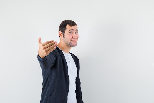 Młody mężczyzna zaprasza do przyjścia w białej koszulce i czarnej bluzie z kapturem zapinanej na suwak i wygląda optymistycznie z przodu.