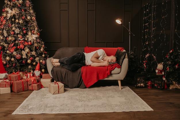 Młody mężczyzna zasnął na kanapie obok choinki. urządzony dom na nowy rok