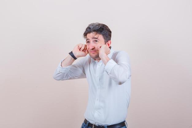 Młody mężczyzna zatyka uszy palcami w białej koszuli, dżinsach i wygląda na przestraszonego