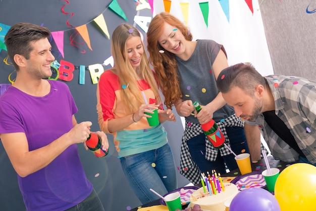 Młody mężczyzna zdmuchujący świeczki na swoim urodzinowym torcie