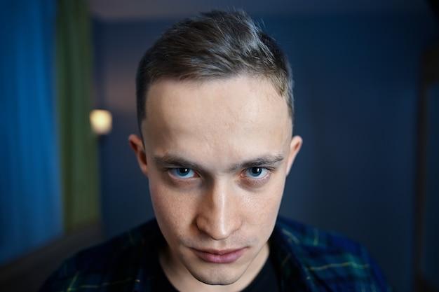 Młody mężczyzna ze schizofrenią paranoidalną wygląda spod brwi z nienawiścią.