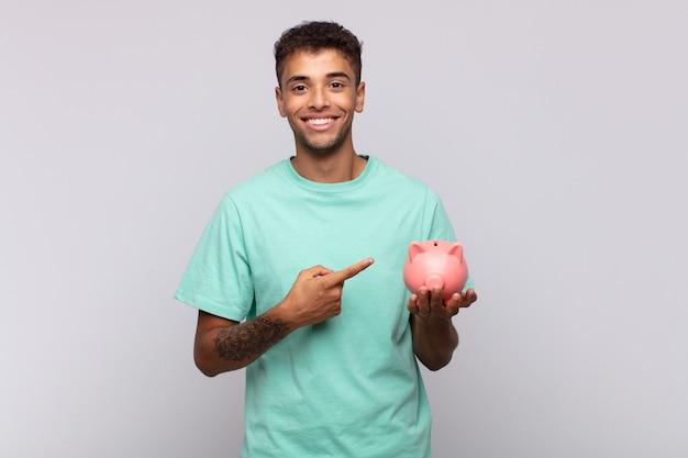 Młody mężczyzna ze skarbonką uśmiechający się radośnie, czujący się szczęśliwy i wskazujący na bok i do góry, pokazujący obiekt w przestrzeni kopii