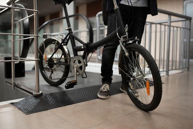 Młody mężczyzna ze składanym rowerem na schodach ruchomych