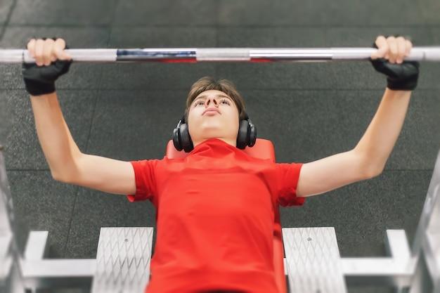 Młody mężczyzna ze słuchawkami na siłowni wyciska sztangę