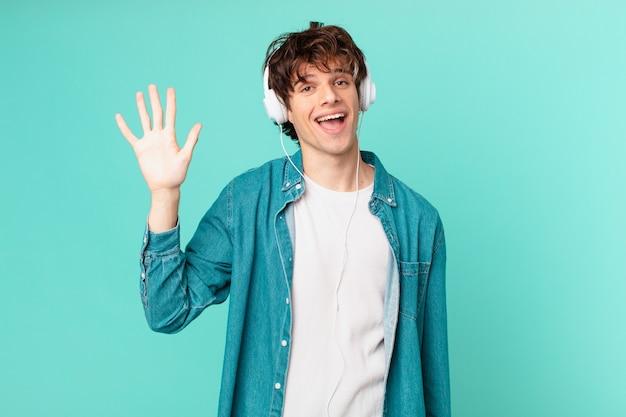 Młody mężczyzna ze słuchawkami uśmiecha się radośnie, macha ręką, wita cię i wita