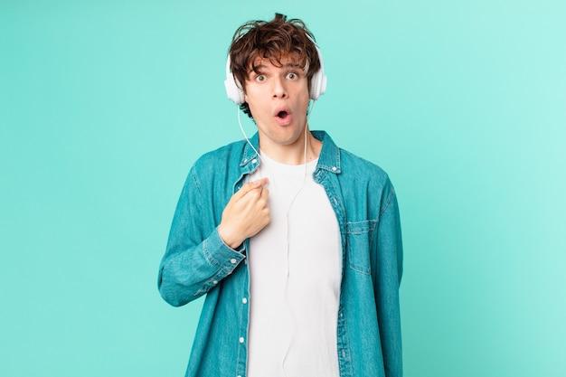Młody mężczyzna ze słuchawkami wyglądający na zszokowany i zaskoczony z szeroko otwartymi ustami, wskazujący na siebie
