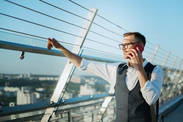 Młody mężczyzna ze smartfonem stojący na tarasie firmy