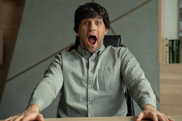 Młody mężczyzna ze zdziwionym wyrazem twarzy siedzi na krześle w biurze